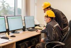 De ingenieurs van de gebiedsdienst inspecteren het systeem van de relaisbescherming met overlapping Royalty-vrije Stock Foto's