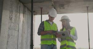 De ingenieursontwerpers bevinden zich in aanbouw op het dak van het gebouw en bespreken het plan en de vooruitgang van stock videobeelden