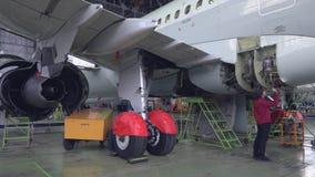 De ingenieurstechnicus inspecteert de binnenkant van de vliegtuigen met een flitslicht 4K stock video