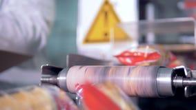 De ingepakte koppen van het wafeltjeroomijs vallen van de transportband stock videobeelden