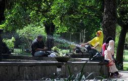 De ingezetenen ontspannen in het park onder een standbeeld Partini Balaikambang Royalty-vrije Stock Fotografie