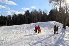 De ingezetenen van de stad kwamen een sneeuwheuvel berijden stock fotografie