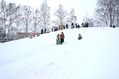 De ingezetenen van de stad met kinderen kwamen aan de sneeuwheuvel stock afbeelding