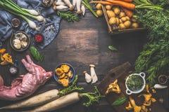 De ingrediënten van de konijnhutspot: groenten, paddestoelen, herby en kruiden op donkere rustieke houten achtergrond Stock Foto