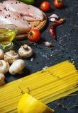 De ingrediënten van deegwaren Kippenborsten, Kersentomaten, spaghettideegwaren en paddestoelen op de donkere steenlijst Stock Afbeelding