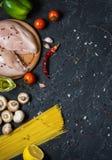 De ingrediënten van deegwaren Kippenborsten, Kersentomaten, spaghettideegwaren en paddestoelen op de donkere steenlijst Royalty-vrije Stock Foto's
