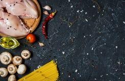 De ingrediënten van deegwaren Kippenborsten, Kersentomaten, spaghettideegwaren en paddestoelen op de donkere steenlijst Royalty-vrije Stock Afbeeldingen