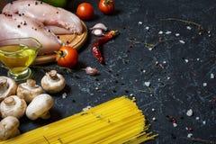 De ingrediënten van deegwaren Kippenborsten, Kersentomaten, spaghettideegwaren en paddestoelen op de donkere steenlijst Stock Fotografie