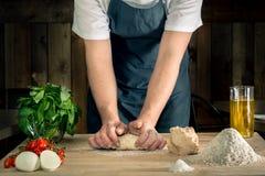 De ingrediënten van het pizzadeeg het maken overhandigt mandmade royalty-vrije stock afbeelding