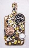 De ingrediënten voor eigengemaakte die hamburger, tonijn, broodje, saus, olijven, kruiden, op een van de knipselraad houten rusti Royalty-vrije Stock Afbeelding