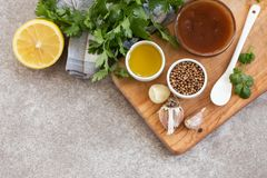 De ingrediënten voor eigengemaakte zoetzure saus met citroen, honing en kruiden op de houten plak schepen achtergrond in royalty-vrije stock afbeeldingen