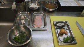 De ingrediënten voor het koken zijn op de metaallijst van de chef-kok De uien, de dille, de rijst en het verse eendvlees zijn op  stock video