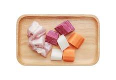 De ingrediënten voor kokende soep hakten wortel, radijs, varkensvleesbeen en purpere aardappel in houten dienblad op witte achter stock afbeelding