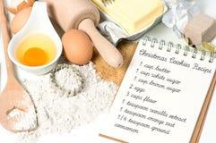 De ingrediënten van Kerstmiskoekjes en open receptenboek Stock Afbeelding