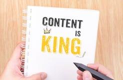 De inhoud is het Koningswerk aangaande het witte notitieboekje van het ringsbindmiddel met handhol Royalty-vrije Stock Foto's