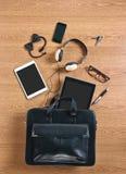 De inhoud van een moderne bedrijfsaktentas op een houten bureau. Royalty-vrije Stock Afbeelding