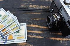 De inkomens in fotografie, een camera en gelddollars zijn op de lijst stock foto's