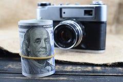 De inkomens in fotografie, een camera en gelddollars zijn op de lijst royalty-vrije stock afbeeldingen