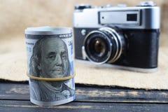 De inkomens in fotografie, een camera en gelddollars zijn op de lijst stock afbeelding