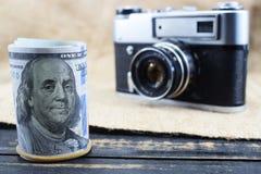 De inkomens in fotografie, een camera en gelddollars zijn op de lijst stock foto