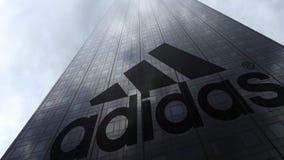 De inschrijving en het embleem van Adidas op een wolkenkrabbervoorgevel die op wolken wijzen Het redactie 3D teruggeven Stock Afbeeldingen