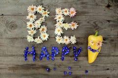 De inschrijving ` is gelukkige ` van bloemen op houten achtergrond met peper in vorm van emoticon Royalty-vrije Stock Afbeelding