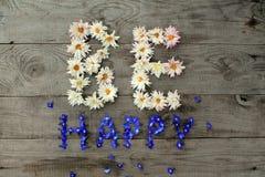 De inschrijving ` is gelukkige ` van bloemen op oude unpainted houten achtergrond met verspreide kleine blauwe bloemen op oppervl Stock Afbeeldingen