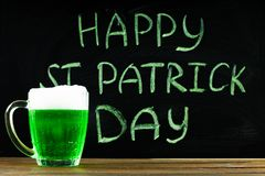 De inschrijving met groen krijt op een bord: Gelukkige St Patrick Dag Een mok met groen bier Royalty-vrije Stock Foto