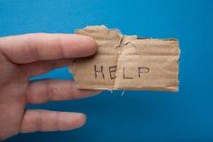 De inschrijving op het oude stuk van karton: 'Hulp 'Armoede en aalmoes stock fotografie