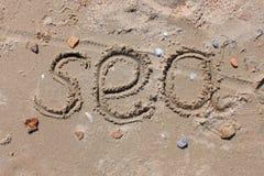 De inschrijving op het strandzand - Overzees, zeeschelpen en stenen royalty-vrije stock afbeeldingen