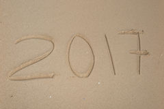 de inschrijving van 2017 op zandig strand wordt geschreven dat Stock Foto's