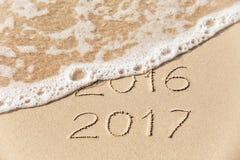 de inschrijving van 2017 van 2016 die in het natte gele strandzand wordt geschreven die zijn Stock Afbeelding