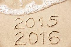 de inschrijving van 2016 van 2015 in het natte gele strandzand wordt geschreven die zijn die Royalty-vrije Stock Afbeeldingen