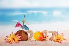 De inschrijving 2017 verfraaide Kerstmiskokosnoot, oranje en tropische bloemen in zand op achtergrond van oceaan Stock Afbeelding