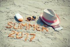 De inschrijvingszomer van 2017, toebehoren voor het zonnebaden en paspoort met muntendollar op zand bij strand, de zomertijd Royalty-vrije Stock Foto's