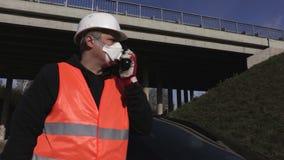 De inspecteur in het luchtmasker bij brug sluit traffi stock footage