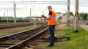 De inspecteur inspecteert controles het automatische schakelaarmechanisme van het spoorweg, van de spoorwegschakelaar mechanisme  stock afbeelding