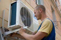 De installateur plaatst een nieuwe airconditioner stock fotografie
