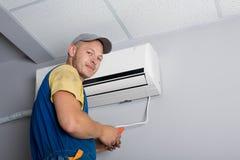 De installateur plaatst een nieuwe airconditioner stock afbeeldingen
