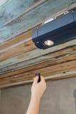 De installatie van garagedeuren Contractant die een mechanische opener van de garagedeur programmeren Stock Fotografie