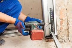 De installatie van garagedeuren De automatische schroevedraaier van het arbeidersgebruik om een bout te bevestigen stock foto