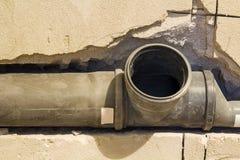 De installatie van rioolpijpen in een badkamers van een flatbinnenland tijdens vernieuwing werkt Grijze plastic rioolbuis voor ge stock afbeeldingen