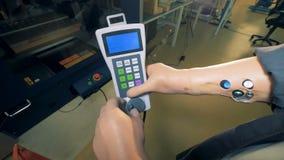 De installatiearbeider met kunstmatige handen houdt een afstandsbediening, omhoog sluit