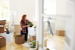 De installaties van de vrouwenverpakking in dozen tijdens verhuizing aan nieuw huis royalty-vrije stock foto