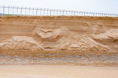 De instorting van het zandduin neer aan een kleine kanaal geopenbaarde textuur binnen royalty-vrije stock foto