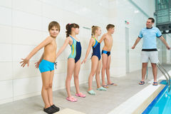 De instructeur en de groep kinderen het doen oefenen dichtbij een zwembad uit Stock Foto