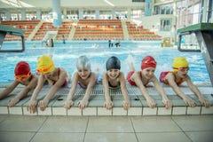 De instructeur en de groep kinderen het doen oefenen dichtbij een zwembad uit Royalty-vrije Stock Fotografie