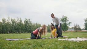 De instructeur leidt jonge vrouwen voor flexibiliteit op - yoga openlucht stock videobeelden