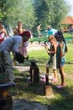De instructeur onderwijst het meisje die op het festival van bla blacksmithing royalty-vrije stock fotografie