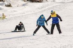 De instructeur onderwijst hoe te op sneeuw te skien bergaf ski?t opleidend op de toevlucht Dombay Royalty-vrije Stock Fotografie
